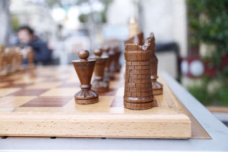a vintage wooden chess set at outdoor table