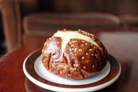 pretzel Kaiser bun with golden sesame seeds