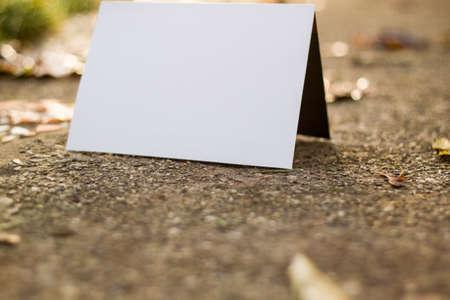 white card on sidewalk in autumn