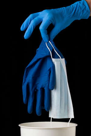 Doctor Hand in a blue medical gloves putting used dirty surgical glove and mask to a garbage bin. Black background