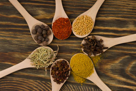 Mix aromatic spices on spoons on wooden background