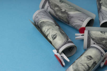 American dollar banknotes rolled on blue background
