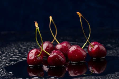 Close-up view of ripe organic cherries with water drops on blue background