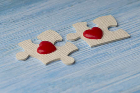 idea that love is a matter of two. Puzzles with the two red hearts on a blue wooden background.