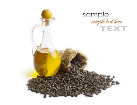 zonnebloem kiemen: zonnebloempitten en plantaardige olie in een fles op een witte achtergrond Stockfoto