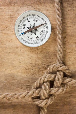Compass with a rope on the background of the old board photo
