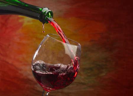 Wein gießt in das Glas der Flasche auf einem farbigen Hintergrund