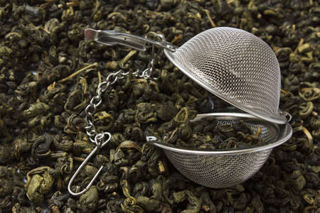 strainer against the background spilled green tea photo