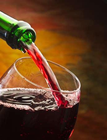 wine pouring: Vino versa nel bicchiere della bottiglia su uno sfondo colorato