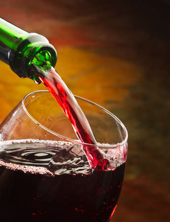 burgundy drink glass: Wine pours into the glass of the bottle on a colored background