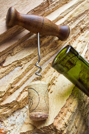 corkscrew with a cork from a bottle on the background texture of the wood Stock Photo - 12660224