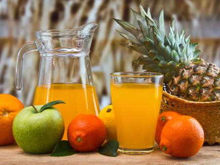 bebidas frias: jugo de naranja en un vaso sobre una mesa con naranjas