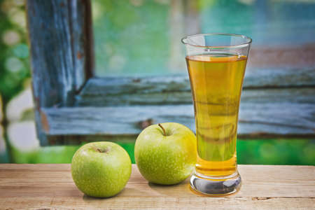 Apple juice in a glass on a table with apples Stock Photo