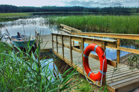 lifeline: boat with a wooden pier with a lifeline in the reeds on the lake