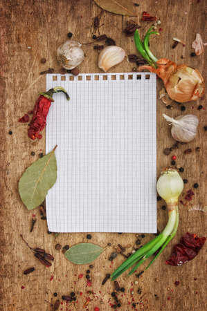notebook to write recipes on the background of a cutting board with spices