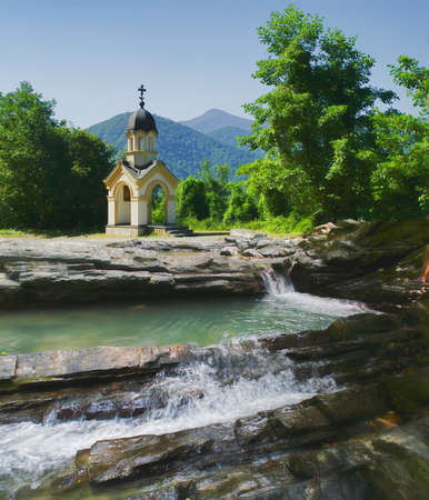 The chapel in the mountains on the banks of the waterfall photo