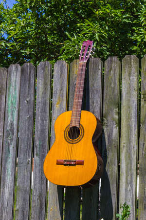 country music: Guitar and the old wagon wheel against a brick wall Stock Photo