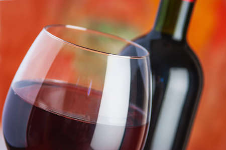 Wein, Glas und die Flasche auf einem farbigen Hintergrund Standard-Bild