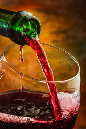 colored bottle: Wine pours into the glass of the bottle on a colored background