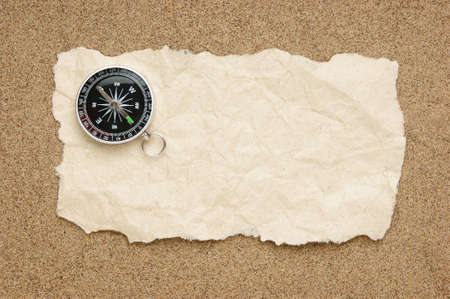 Compass on old sheet crumpled paper against the background of sand Stock Photo - 15905998