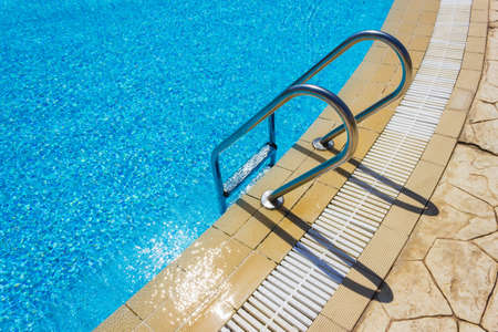 Grab bars ladder in the blue swimming pool Stock Photo - 15905875