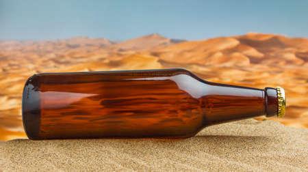 bottle of beer in desert on the hot sand photo