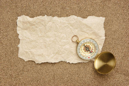 Compass on old sheet crumpled paper against the background of sand Stock Photo - 16567835