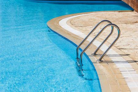 Grab bars ladder in the blue swimming pool Zdjęcie Seryjne