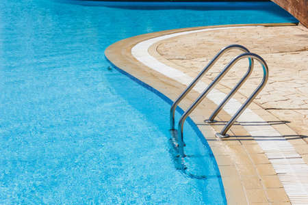 Grab bars ladder in the blue swimming pool Standard-Bild