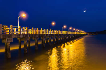 Pier at night with yellow lights on a background of blue sky stretching into the sea photo