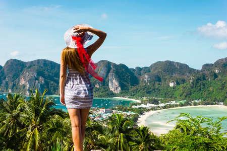 Das Mädchen an der Anlage in einem Kleid und Hut auf dem Hintergrund der Buchten der Insel Phi Phi Standard-Bild
