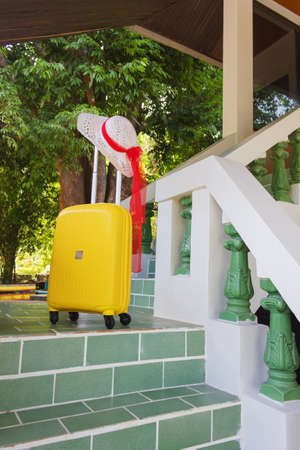 lugage: Orange travel case and sun hat on the stairs at the entrance to the hotel Stock Photo