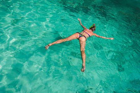 Girl swimming in the clear water of the sea with a mask and snorkel photo