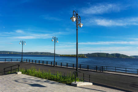 welded: Street lights on the promenade on the shore of the great river Stock Photo