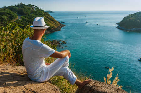 generation gap: The man at the resort in a white suit and hat sitting on a rock on the sea background