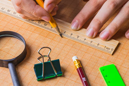 draftsman draws on a ruler on the graph paper photo