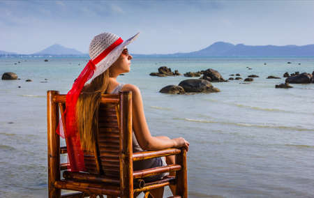 young girl sitting on a chair and looks at the sea