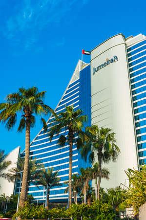 DUBAI, Emiratos �rabes Unidos - 15 de noviembre: Las palmeras ondeando en el viento y el tablero de ajedrez gigante en frente de Jumeirah Beach Hotel, resort de lujo en forma de onda, conocida Dubai se�al, el 15 de noviembre de 2012, Dubai, Emiratos �rabes Unidos.