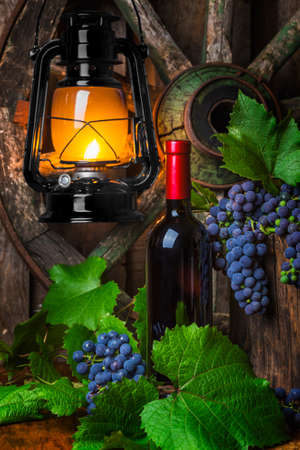 Bottle of red wine with grapes on a background of a kerosene lamp photo