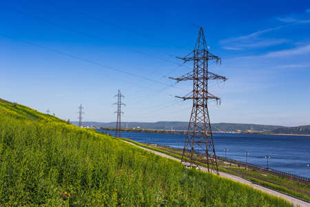 High-voltage power line on the shore of the river photo