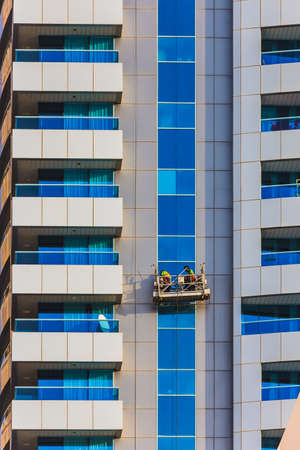 window cleaner: window cleaners in a gondola cleaning the windows of a corporate office skyscraper.