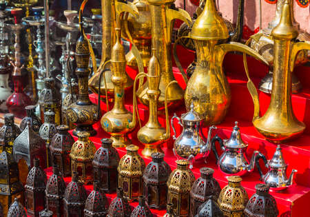 row of shiny traditional coffee pots and lamp at the souq in Dubai. photo