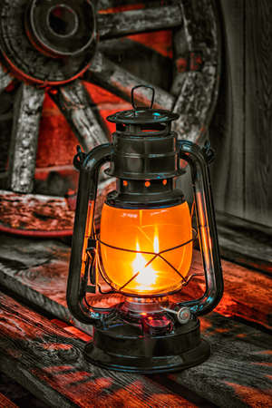 kerosene lamp on the old wooden boards against the background wagon wheel photo