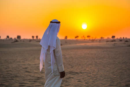 middle eastern clothing: Arab in the Arabian desert on a hot sunny day Stock Photo