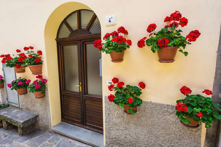 ITALY - JUNE 23, 2014: Windows and doors in an old house decorated with flower pots and flowers