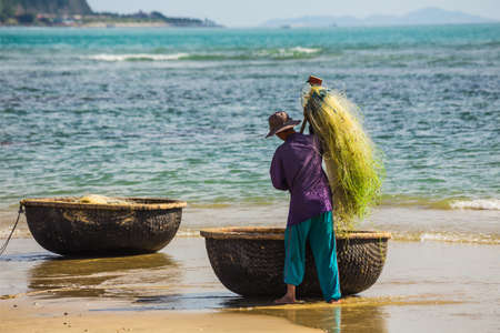 livelihood: NHA TRANG, VIETNAM - NOV 28: Unidentified fishermen is working on the beach in Nha Trang, Vietnam. On Nov 28, 2014.