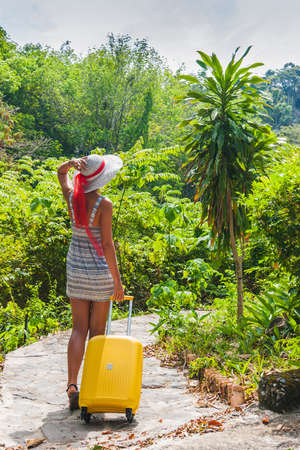 on looker: Girl with a yellow suitcase on a resort in Thailand