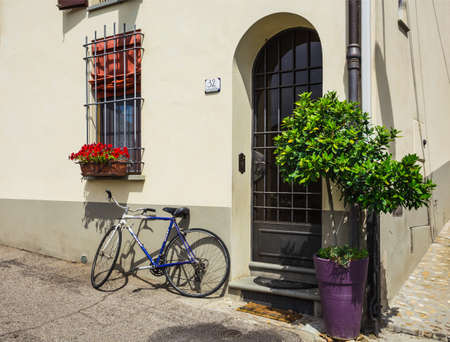 TUSCAN, ITALY.23 June 2014. bike loaded with flowers standing in front of an old door in a traditional Italian medieval city center. Tuscany, Italy.