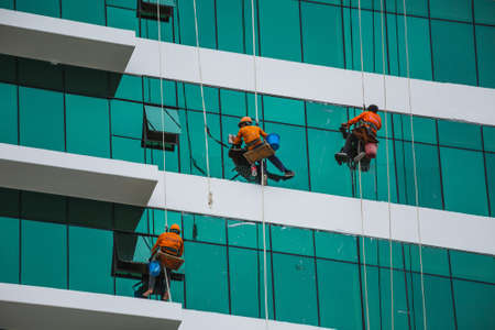 worker cleaning high tower in big city, Vietnam. Stock Photo