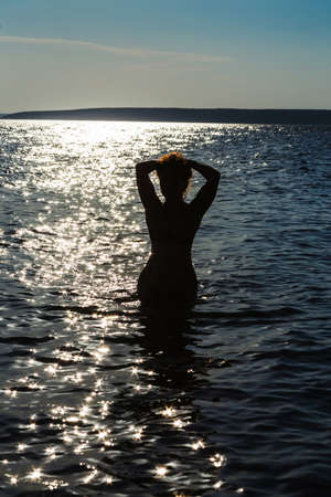 butch: Silhouette of a young slim girls on the beach at sunset (sunrise)